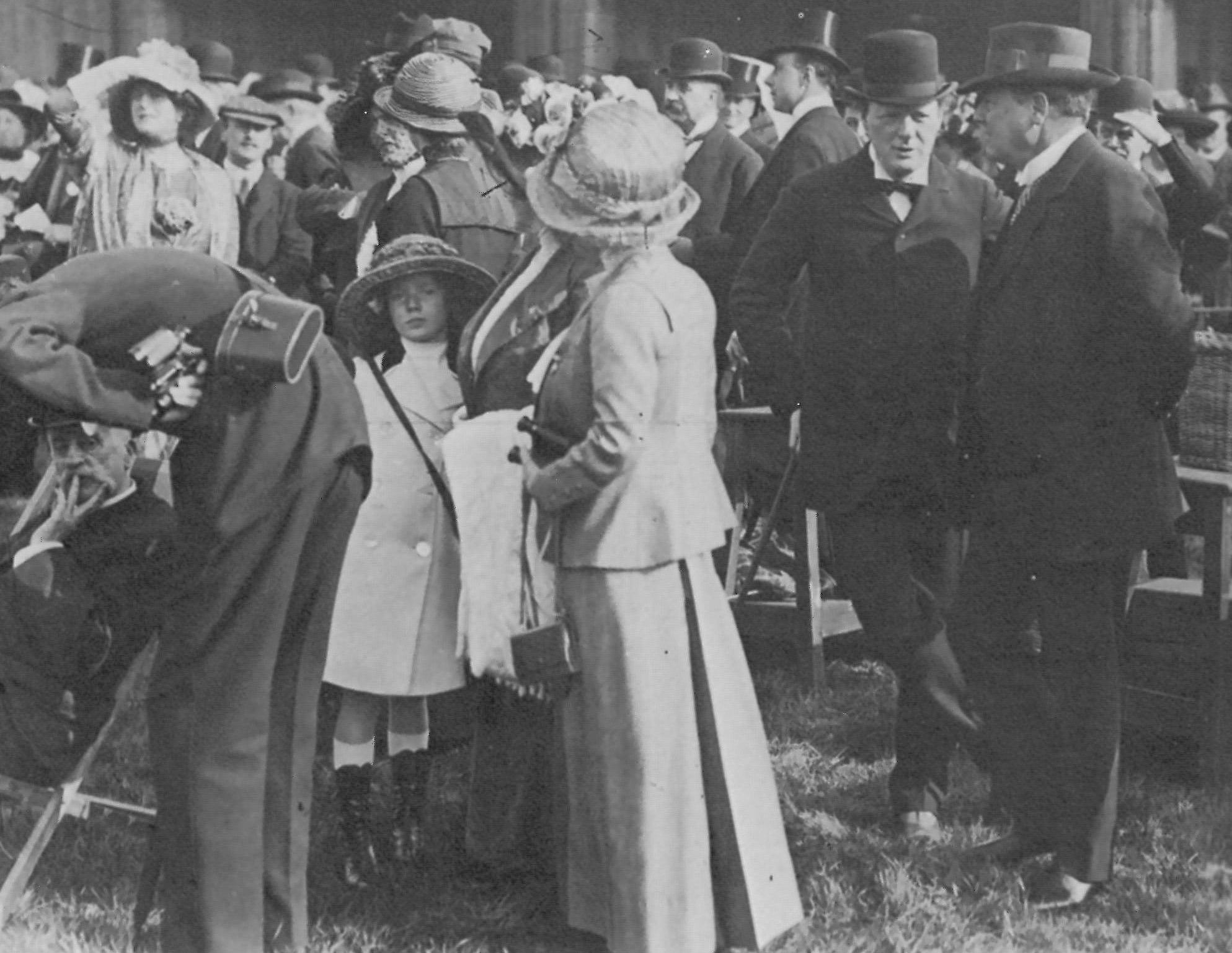 Home Secretary Churchill conversing with Lord Northcliffe, Hendon, 12 May 1911. Clementine Churchill is at left shading her eyes.